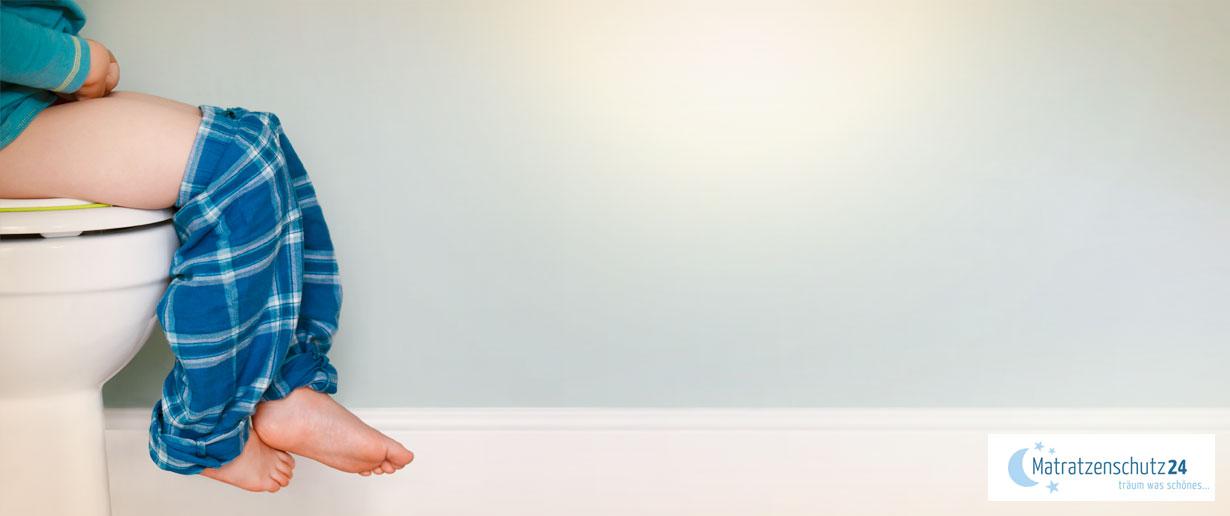 Kind sitzt auf WC und lässt die Beine baumeln