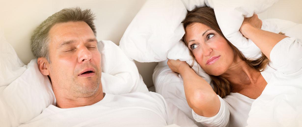 Bild, das eine Frau im Bett zeigt, die sichtlich genervt vom Schnarchen ihres Mannes ist