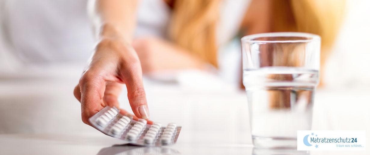 Frau nimmt Tabletten im Bett