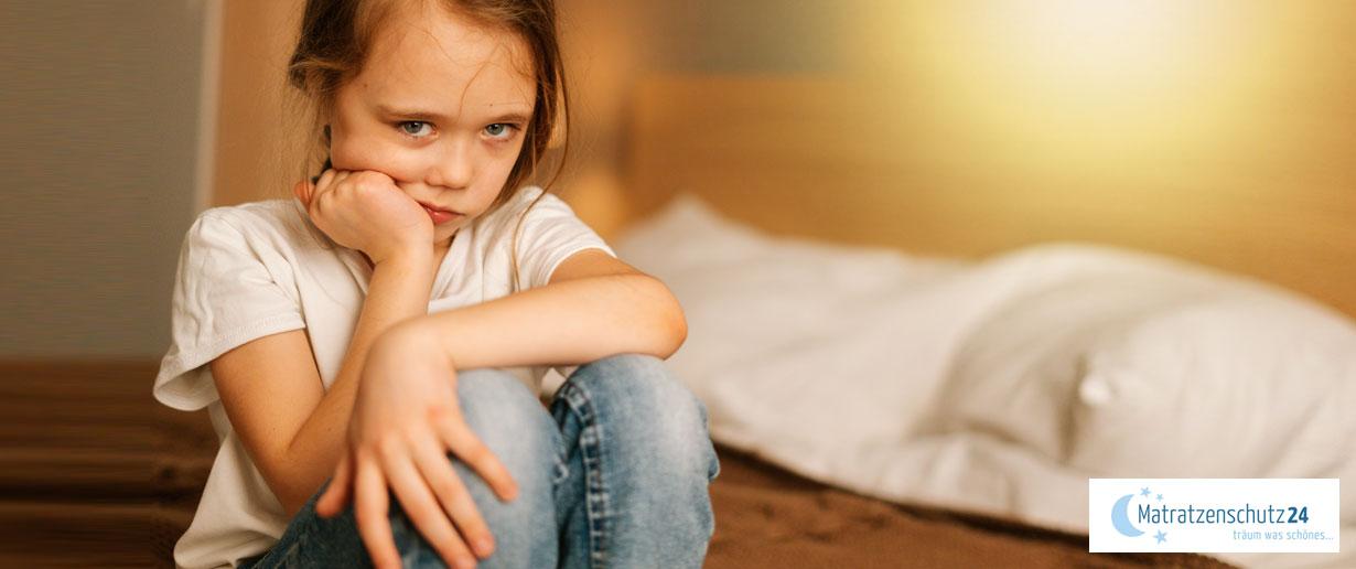 Trauriges Mädchen (Schulkindalter) sitzt auf Bett