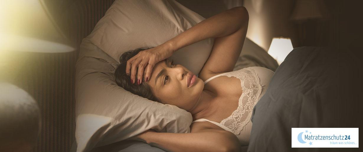 verzweifelte Frau liegt wach im Bett