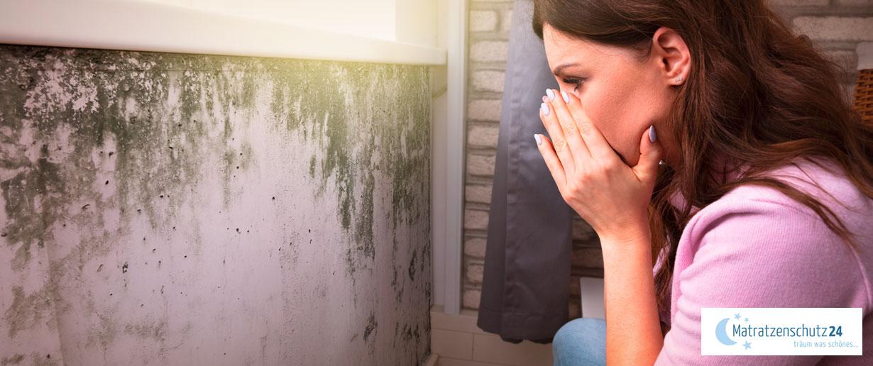 Frau guckt fassungslos auf die schimmelige Wand