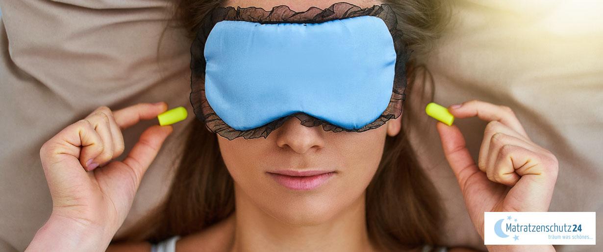Frau liegt mit Schlafmaske und Ohrstöpseln im Bett