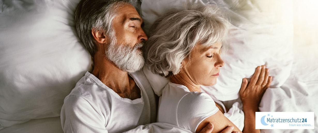 Älteres Ehepaar liegt im Bett und schläft