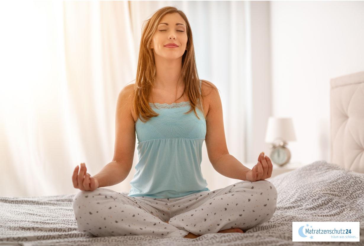 Frau macht Yoga im Bett