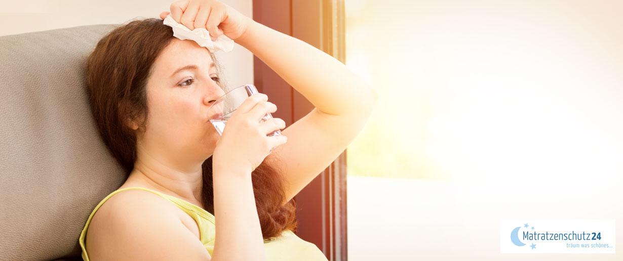 Frau tupft sich Schweiß von der Stirn und trinkt ein Glas Wasser
