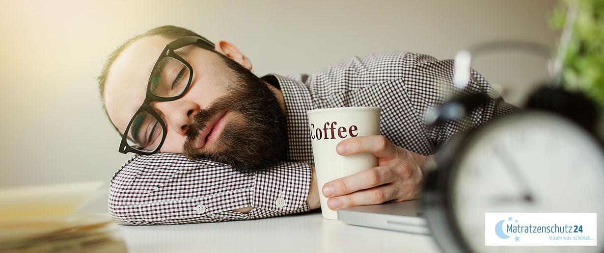 Mann schläft mit Kaffeebecher in der Hand