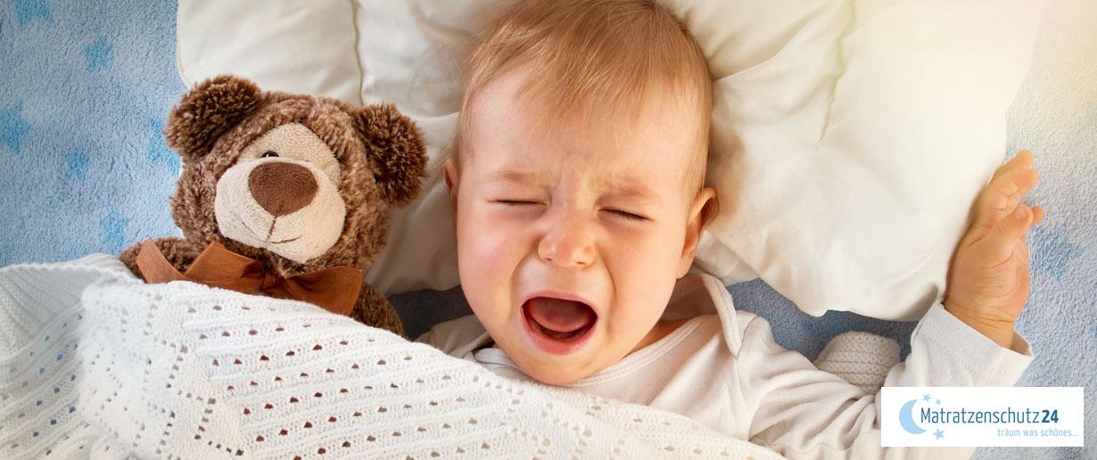 Weinendes Baby liegt mit Teddy im Bett