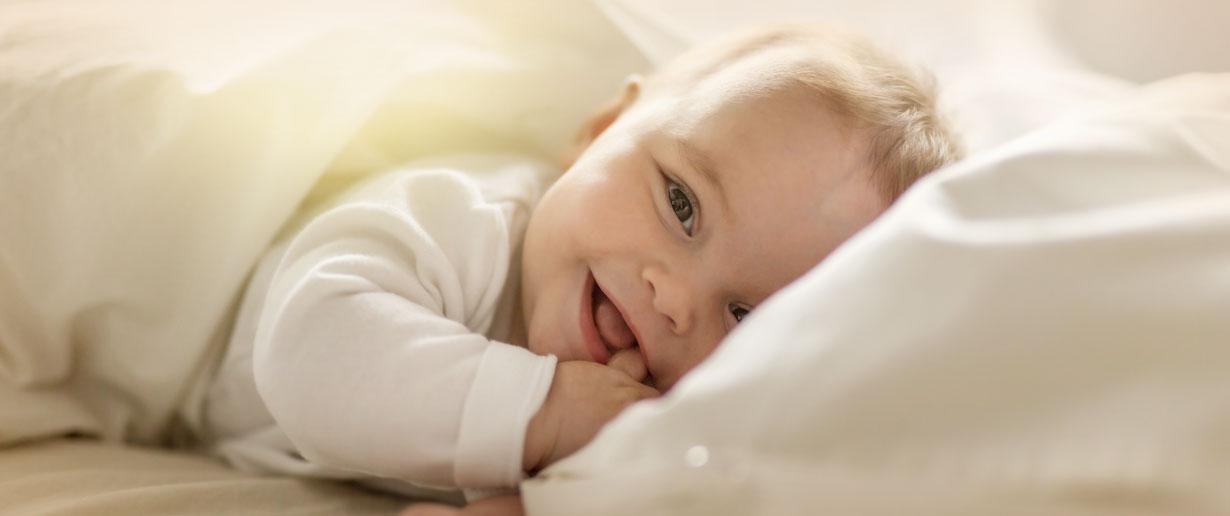 Baby lächelt freundlich aus dem Bett