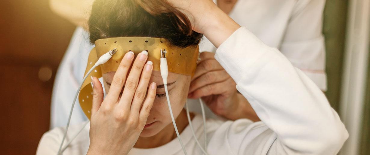 Bild zeigt eine junge Frau im Schlaflabor, bei der die Hirnströme gemessen werden