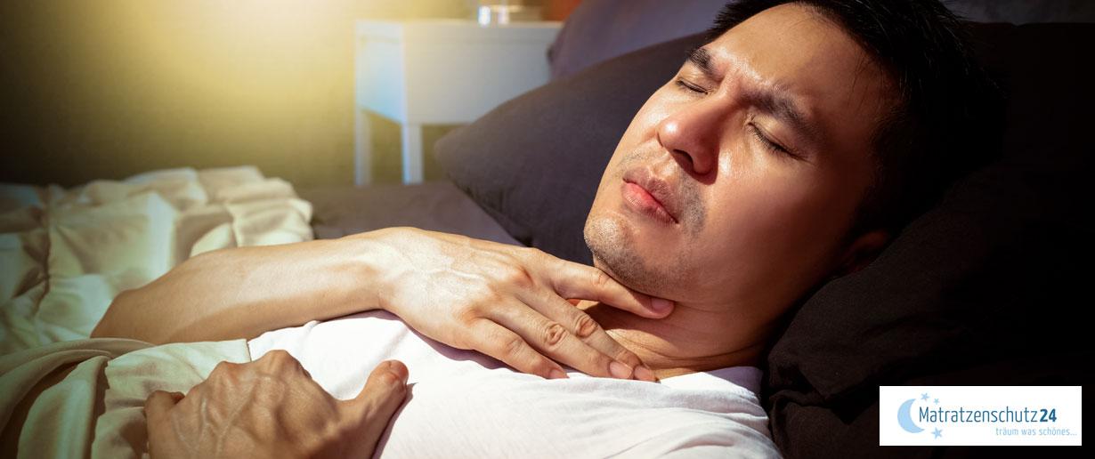 Mann liegt mit Halsschmerzen im Bett