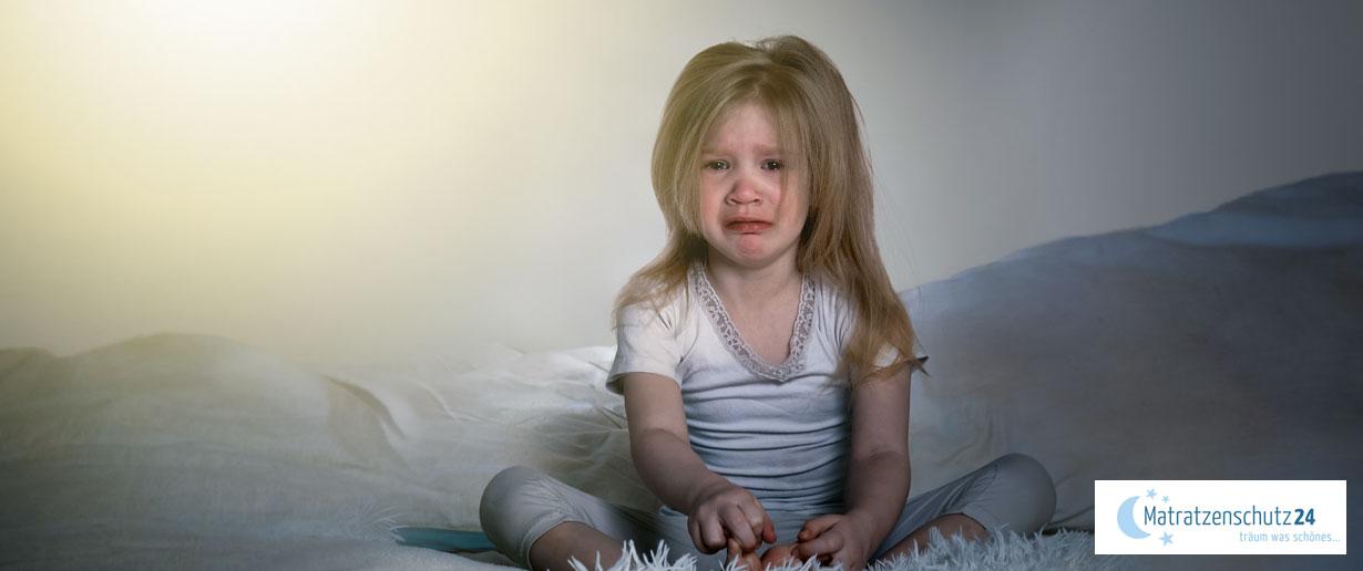 Kleines Kind sitzt im Bett und weint