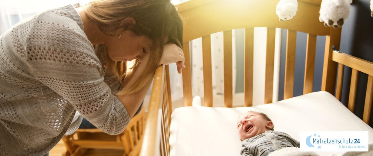 Mutter steht am Bett ihres weinenden Babys