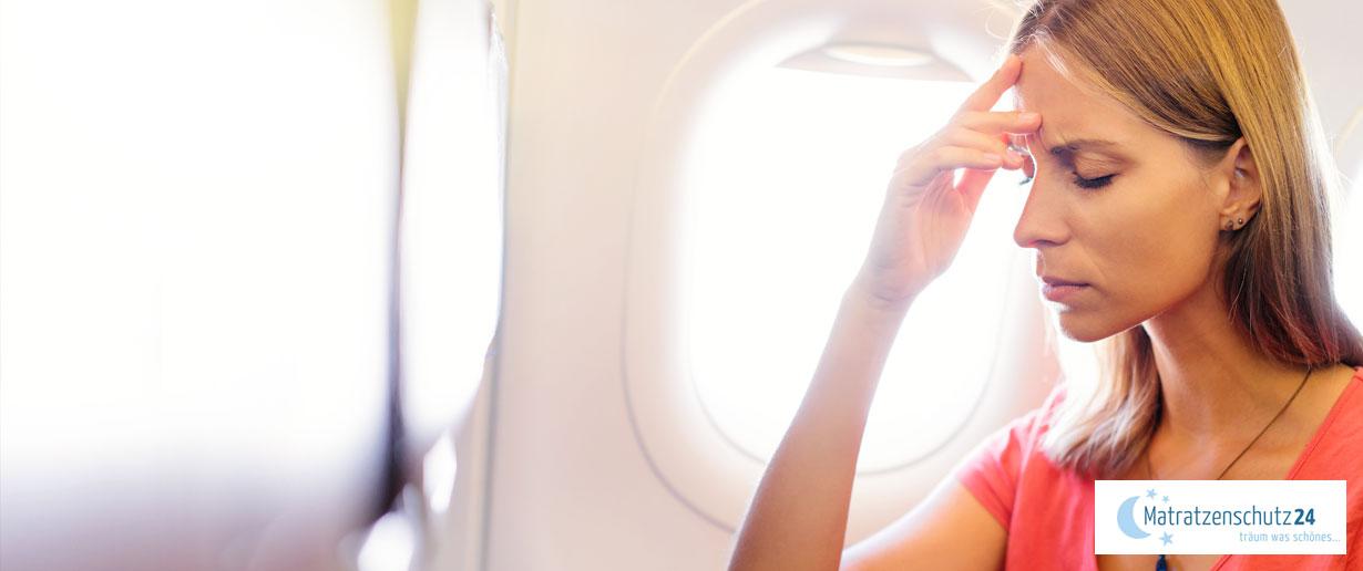 Frau mit Kopfschmerzen im Flugzeug