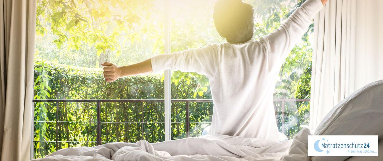 Mann sitzt auf Bett und streckt sich morgens nach dem Aufwachen