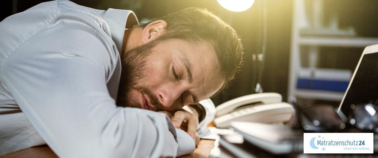 Mann schläft auf dem Schreibtisch