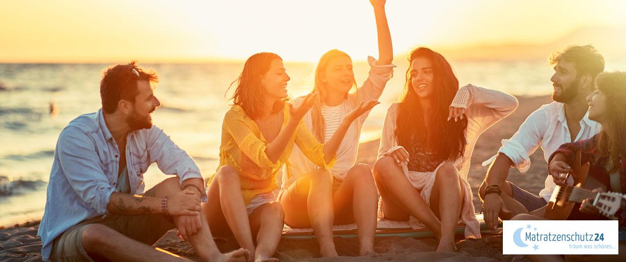 Junge Menschen sitzen beim Sonnenuntergang am Strand