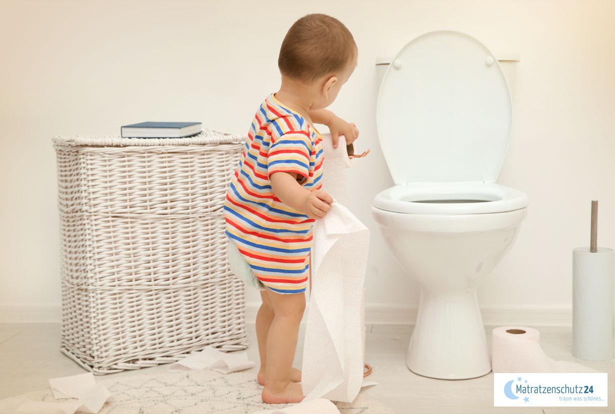 Kleinkind steht vor WC und spielt mit Toilettenpapier