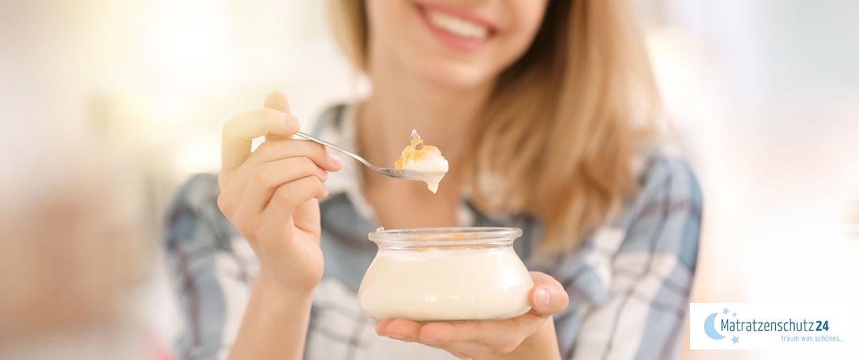 Frau isst lächelnd einen leichten Joghurt