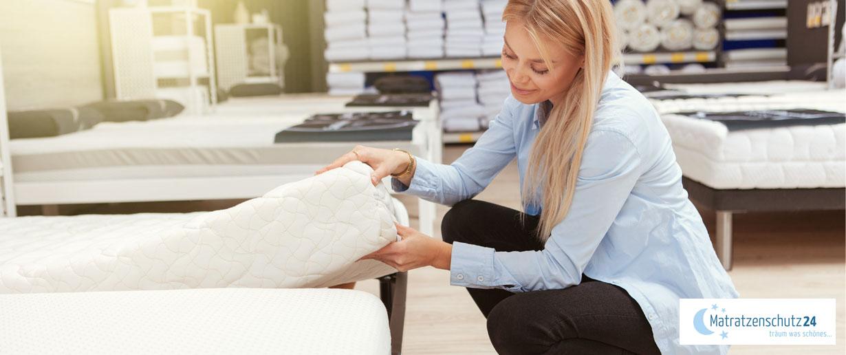 Eine Frau sucht im Fachgeschäft nach einer passenden Matratze