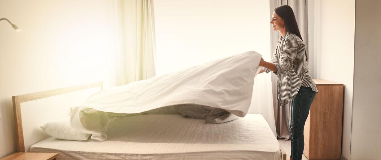Frau wechselt die Bettwäsche