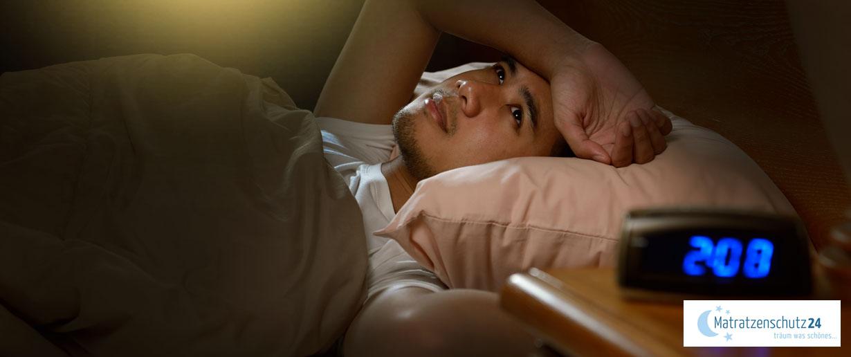 Mann liegt nachts wach im Bett