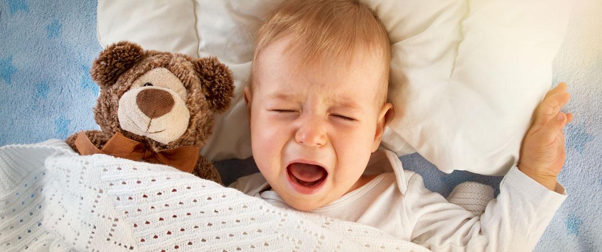 Baby liegt im Bett und schreit