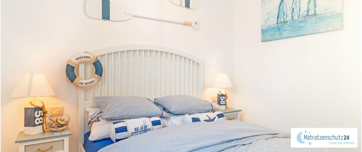 maritimes Schlafzimmer mit Küsten-Deko (Leuchtturm, Schwimmring, Paddel) und blau-weißen Streifen
