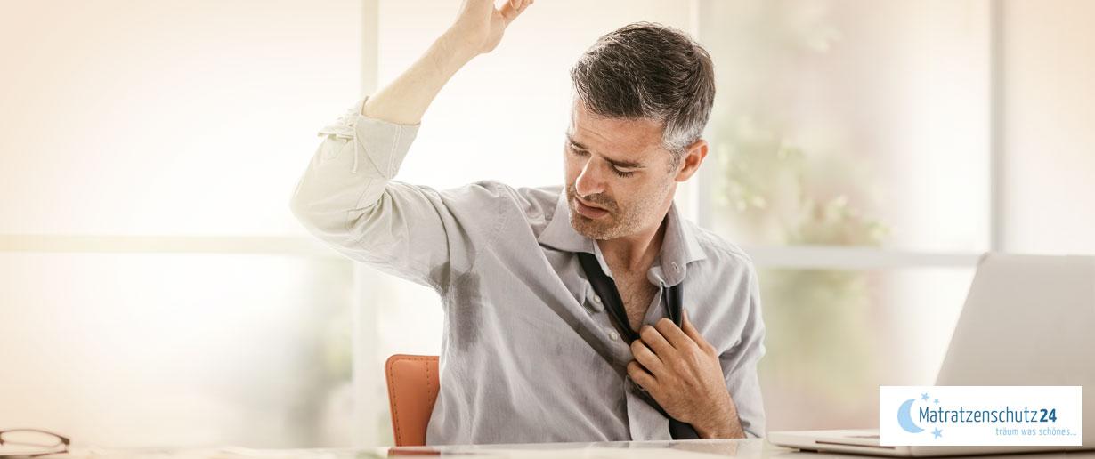 Mann sitzt am Laptop und schaut auf die Schweißflecken unter seinen Achseln