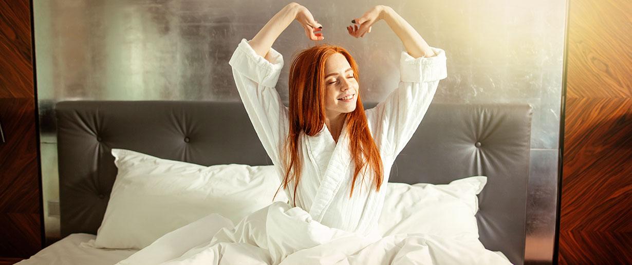 Frau sitzt morgens auf dem Bett und streckt sich