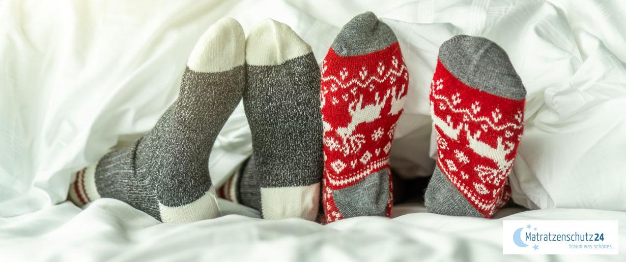 Zwei Paar Füße mit dicken, winterlichen Stricksocken unter der Bettdecke