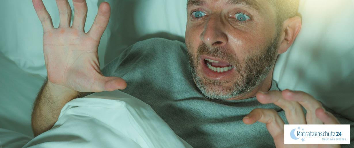 Ein Mann hat eine Panikattacke im Bett