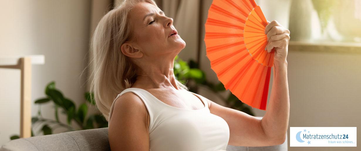 Frau in den Wechseljahren fächert sich Luft zu